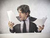 Shocked businessman staring at some documents