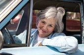stock photo of senior-citizen  - Happy senior out driving the old car - JPG