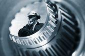 engineer seen through the shaft of a giant gear wheel, duplex blue toning concept