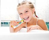 stock photo of toothpaste  - Little girl brushing teeth in bath - JPG