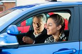 Driving School - Young woman steer a car, maybe she has a driving test perhaps she exercises the par
