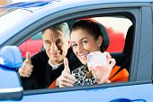 Driving School - Young woman steer a car, maybe she has a driving test, she holding proudly her driv