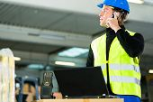 Warehouseman with protective vest, scanner and laptop in warehouse at freight forwarding company usi
