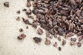 Close-up of a pile of raw cacao nibs on a rough white painted barn wood background
