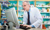 Portrait of a pharmacist using a desktop computer