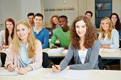 Many happy students sitting in university course classroom