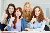 Four attractive happy women holding their thumbs up in university