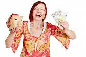 Successful woman cheering with piggy bank and Euro money bills