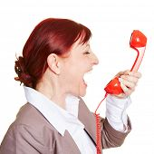 Angry business woman screaming loudly in a red phone receiver