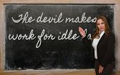 Teacher Showing The Devil Makes Work For Idle Hands On Blackboard