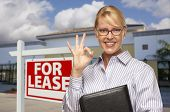 Smiling Businesswoman with Okay Sign In Front of Vacant Office Building and For Lease Real Estate Si