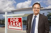 Handsome Businessman In Front of Vacant Office Building and For Lease Real Estate Sign.