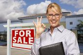 Smiling Businesswoman with Okay Sign In Front of Vacant Office Building and For Sale Real Estate Sig
