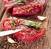 stock photo of peppercorns  - Raw beef steak on a dark wooden table - JPG