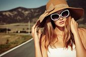 stock photo of independent woman  - Beautiful young woman posing on a road over picturesque landscape - JPG