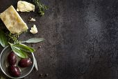 Food background with parmesan cheese, fresh herbs and olives, over dark slate.  Lots of copy space.