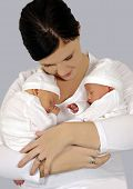 stock photo of twin baby girls  - Young mother with twin babies in white clothing - JPG