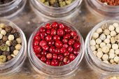 picture of peppercorns  - Horizontal top focus shot of red peppercorns in small container next to other peppercorns on stone surface - JPG