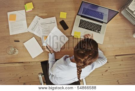 Businesswoman Working At Her Office Desk With Documents And Laptop poster