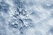 Winter, Christmas minimal elegant background. Snowflake on snow, blue tint.