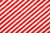image of diagonal lines  - A crumpled sheet of Christmas wrapping paper in a red and white stripe pattern for use as a background - JPG