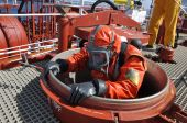 picture of decontamination  - man in protective suit on deck of chemical tanker entering in cargo tank for cleaning operation - JPG