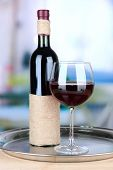 Wine glass and bottle on bright background