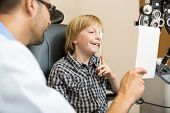 Young boy at optometrist taking vision test using occluder