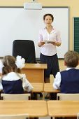 Teacher talks near chalkboard and pupils listen her at desks in classroom at school.