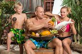 A family of three on a sandy beach with a basket of fruit and fish in fathers hand