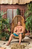 Muscular man resting in wooden chair on the sandy beach near the wooden house