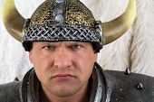 A strict man in costume viking with a helmet