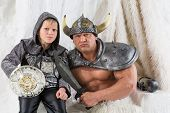 A muscular man with young son in costume viking with a sword with menacing faces