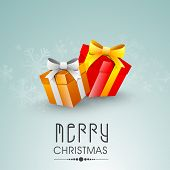 Merry Christmas celebration greeting card or invitation card with gift boxes wrapped with ribbon on blue background.