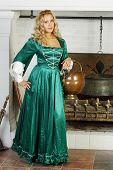 Pretty woman in green medieval costume with pot on hand stands near fireplace with logs and boiler.