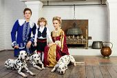 Young father, mother and little son in medieval costume stand near fireplace with three dalmatians o