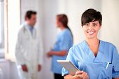 stock photo of nurse uniform  - Portrait of a lovely latin nurse on blue uniform standing and smiling on medical team background - JPG