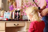stock photo of console-mirror  - Back of pretty blonde little girl and hands of hairdresser with curling iron - JPG