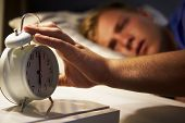 Teenage Boy Waking Up In Bed And Turning Off Alarm Clock