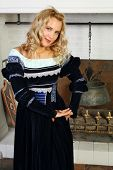 Pretty woman in medieval costume stands near fireplace and looks at camera.
