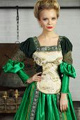 Beautiful woman in green medieval costume stands near chimney with logs and boiler.