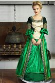 stock photo of chimney  - Beautiful young woman in green medieval costume stands near chimney with boiler - JPG
