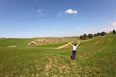 The wonderful spring day in southern Israel. An elderly woman enthusiastically welcomed flying in th