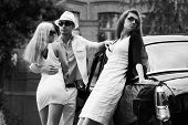Young couple and jealous girl at the retro car