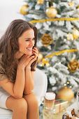 Portrait Of Happy Young Woman With Latte Macchiato Sitting Near Christmas Tree