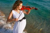 Beautiful Girl Playing Violin On Sea Background