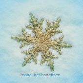 picture of a golden snowflake-shaped christmas star on the snow and the sentence frohe weihnachten, merry christmas in german, with a retro effect