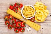 uncooked pasta with tomatoes and garlic on wooden background