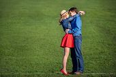 stock photo of jeans skirt  - young couple embracing on a green lawn - JPG