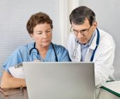 stock photo of medical doctors  - Doctor And Nurse Talking and Working at Laptop Computer In Office - JPG